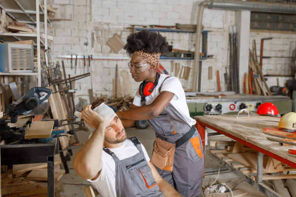 A female worker tends to a male worker with a head injury