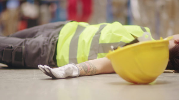 Worker lying on the floor. Accident in warehouse
